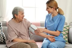 Кровяное давление медсестры измеряя пожилой женщины внутри помещения стоковые изображения rf