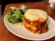 Крок месье - самый известный французский тост с ветчиной и сыром, который служат с зелеными цветами салата стоковое изображение rf
