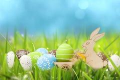 Кролик пасхи с яичками в тележке в зеленой траве с голубым небом стоковое фото rf