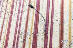 Кроша шелушась старый paintwork на старой и старея стене арендуемого дома с уличным фонарем Картина начинает увядать и стоковые фотографии rf