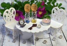 Крошечная таблица с стульями и 2 бутылки с бирками едят меня, выпивают меня Стоковая Фотография RF
