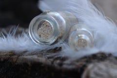 крошечные бутылки песка покрытые с мягкими пер белых птиц Стоковое Фото