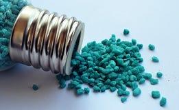 Крошечные голубые камни разливая от стеклянной бутылки Стоковое Изображение RF