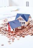 Крошечные миниатюры домов среди монеток Стоковое Фото