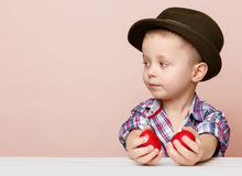 Крошечный мальчик в шляпе смотрит налево в руках держа красную пасху Стоковые Фото