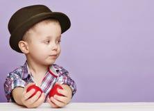 Крошечный мальчик в шляпе смотрит правым в руки держа красный цвет Стоковые Фотографии RF