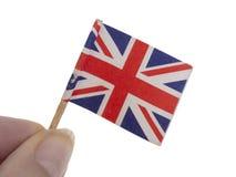 Крошечный, поколоченный и поврежденный Юнион Джек, флаг Великобритании в пальцах, изолированных на белой предпосылке стоковое изображение