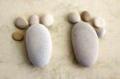 2 крошечных каменных фута и 10 пальцев ноги на бежевой предпосылке, камне в форме ног человека Стоковые Фото
