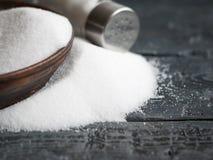 Крошить молотилка соли точная от чашек и шейкеров соли на деревянном столе Стоковая Фотография