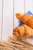 2 круассаны и уш пшеницы на покрашенной белизне Стоковая Фотография RF