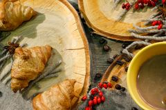 Круассаны и чашка кофе на деревянной поверхности среди шерстяного одеяла и красных ягод Повод осени Стоковые Фото