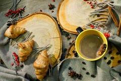 Круассаны и чашка кофе на деревянной поверхности среди шерстяного одеяла и красных ягод Повод осени Стоковое Фото