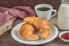 Круассаны на плите с кофейной чашкой, бутылкой молока и плодоовощ сжимают стоковая фотография