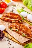 Круассаны с беконом, сыром и овощами на деревянной доске стоковое фото rf