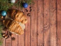 Круассан завтрака рождества на салфетке деревянное предпосылки темное Космос экземпляра украшений рождества стоковое фото