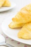 Круассан или хлеб на белом блюде на Placemat с концом ложки вверх Стоковая Фотография