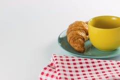 Круассан на зеленом блюде с желтой белизной красного цвета кофе и ткани чашки чередуя Стоковые Изображения RF