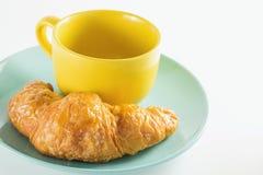 Круассан на зеленом блюде с желтым кофе чашки Стоковая Фотография