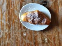 Круассан покрыл с сахаром замороженности в белом блюде на винтажное деревянном стоковые фотографии rf