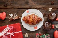 Круассан служил для завтрака на деревянном столе, подарка праздника Стоковое Изображение RF