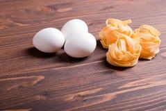 Круга макаронных изделий сырцовые 3 и 3 белых яичка на коричневом деревянном t Стоковое Изображение