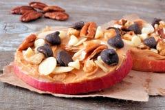 Круги Яблока закрывают вверх с арахисовым маслом, шоколадом и гайками стоковое фото