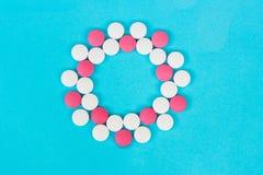 Круглая рамка белых и красных таблеток на светлом - голубая предпосылка стоковые изображения