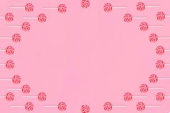 Круглая рамка леденцов на палочке с красными и белыми нашивками на розовой предпосылке стоковые изображения rf