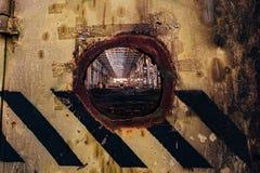Круглое отверстие в grungy, который слезли железной двери покрашенной в желтой и черной нашивке Взгляд к покинутой фабрике через  стоковые фото