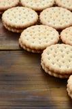 Круглое печенье сандвича с завалкой кокоса лежит в больших количествах на коричневой деревянной поверхности Фото съестных обслужи стоковая фотография