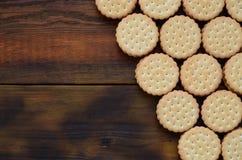 Круглое печенье сандвича с завалкой кокоса лежит в больших количествах на коричневой деревянной поверхности Фото съестных обслужи стоковое изображение rf