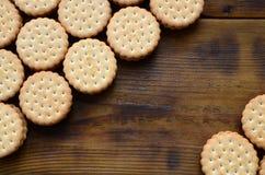 Круглое печенье сандвича с завалкой кокоса лежит в больших количествах на коричневой деревянной поверхности Фото съестных обслужи Стоковые Фото