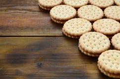 Круглое печенье сандвича с завалкой кокоса лежит в больших количествах на коричневой деревянной поверхности Фото съестных обслужи Стоковые Изображения RF