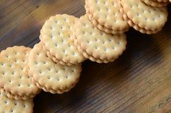 Круглое печенье сандвича с завалкой кокоса лежит в больших количествах на коричневой деревянной поверхности Фото съестных обслужи Стоковые Фотографии RF