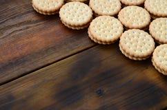 Круглое печенье сандвича с завалкой кокоса лежит в больших количествах на коричневой деревянной поверхности Фото съестных обслужи Стоковое Изображение