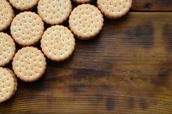 Круглое печенье сандвича с завалкой кокоса лежит в больших количествах на коричневой деревянной поверхности Фото съестных обслужи Стоковое Фото