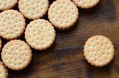 Круглое печенье сандвича с завалкой кокоса лежит в больших количествах на коричневой деревянной поверхности Фото съестных обслужи Стоковые Изображения