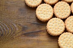 Круглое печенье сандвича с завалкой кокоса лежит в больших количествах на коричневой деревянной поверхности Фото съестных обслужи Стоковая Фотография RF