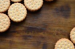Круглое печенье сандвича с завалкой кокоса лежит в больших количествах на коричневой деревянной поверхности Фото съестных обслужи Стоковое фото RF