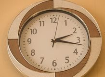 Круглые настенные часы показывают времени 2 часа и 15 минут на светлой шкале Стоковые Фотографии RF