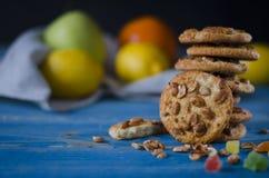 Круглые оранжевые печенья с красочными candied плодами и кусок сочного апельсина лежа на деревянном столе стоковая фотография rf