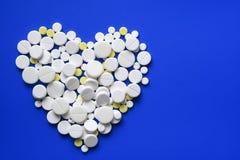 Круглые таблетки аранжировали конспект на голубой предпосылке цвета Пилюльки для дизайна Концепция здоровья, здорового образа жиз Стоковое Фото