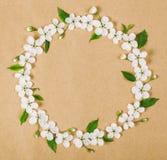 Круглый венок рамки сделанный из белых цветков весны и листьев зеленого цвета на предпосылке коричневой бумаги Плоское положение Стоковое Фото