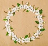 Круглый венок рамки сделанный из белых цветков весны и листьев зеленого цвета на предпосылке коричневой бумаги Плоское положение Стоковые Изображения RF