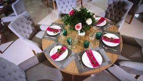 Круглый деревянный стол украшенный с цветочными композициями сделанными из белых плит с розовыми салфетками вокруг которых там акции видеоматериалы