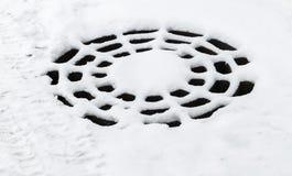 Круглый люк -лаз сточной трубы со снегом стоковые изображения