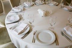 Круглый стол предусматриван с белой скатертью стоковое изображение