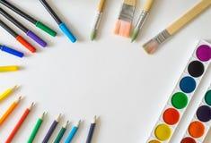 Круглая рамка, сделанная от щеток картины, ручки войлок-подсказки, краски акварели, карандаши на белой предпосылке Стоковое фото RF