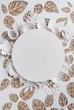 Круглая рамка с цветками белой бумаги на предпосылке листьев Стоковые Изображения RF
