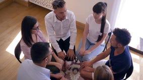 Круг доверия, люди группы на усаживании терапевтической сессии наоборот на стульях рядом друг с другом сток-видео